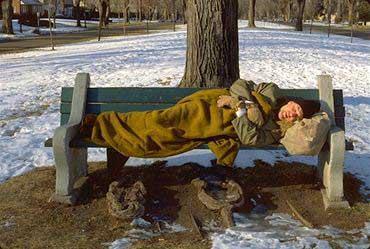 Zwerver slapend op bankje in sneeuw