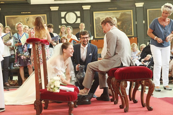 Het bruidspaar wast de voeten van een draaideurcrimineel (Anton de W.) die toevallig in de buurt was. Foto: Hester Fotografie